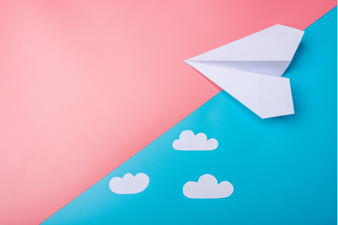 Paper airplane on a pink and blue paper background