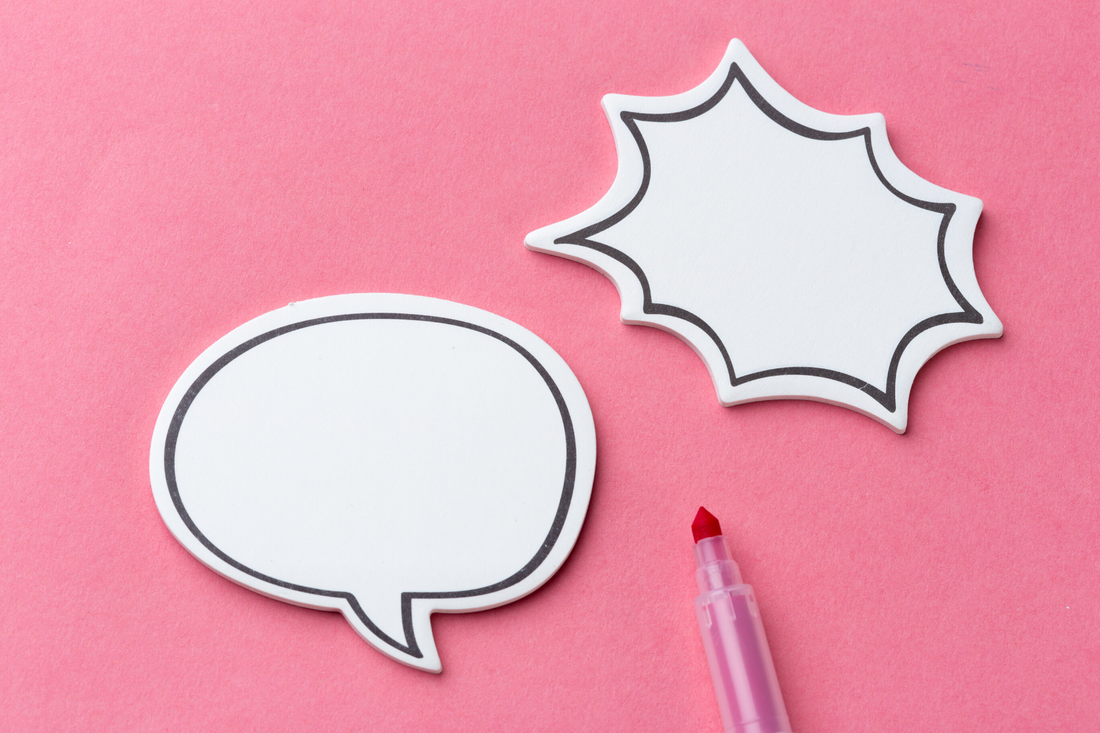 Word bubbles cut out of paper on a pink paper background