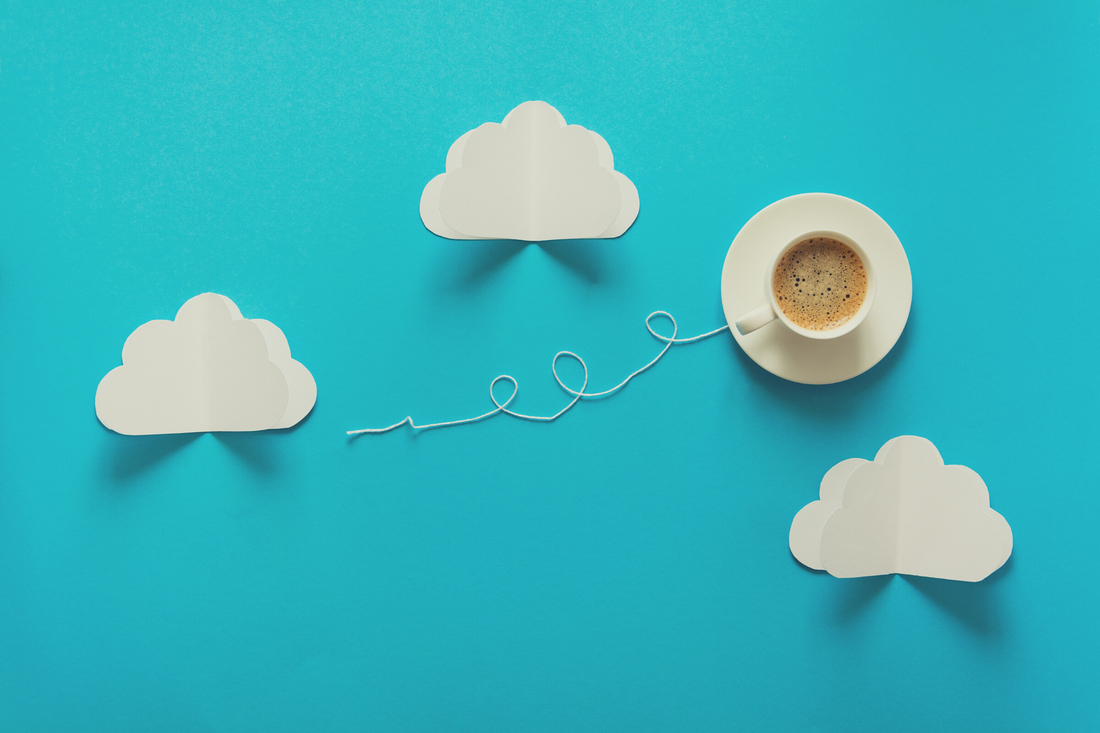 Top-down view of clouds cut from paper and a cup of coffee sailing through them, leaving a trail of string