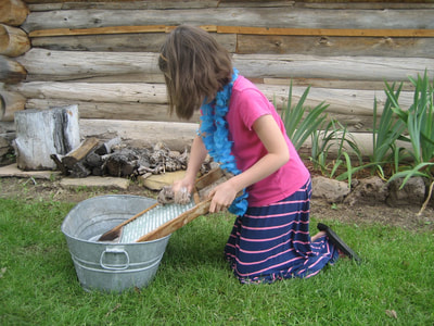 Young student using a homestead era washboard
