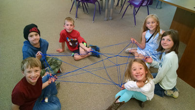 Young students using string to learn about the web of life