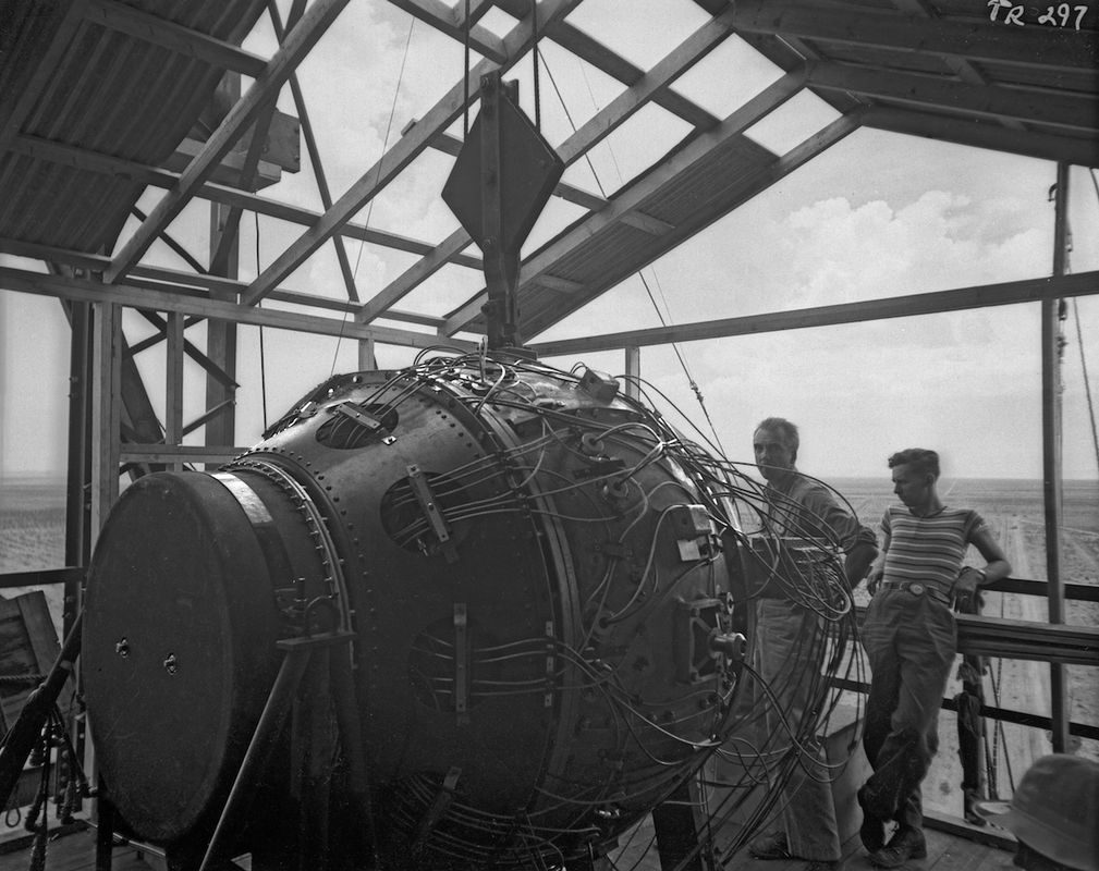 The Gadget is suspended by tackle at the top of the tower. Norris Bradbury (left) and an unidentified Project employee stand behind the Gadget. Los Alamos Historical Society Photo Archives, LANL Collection, TR Series.