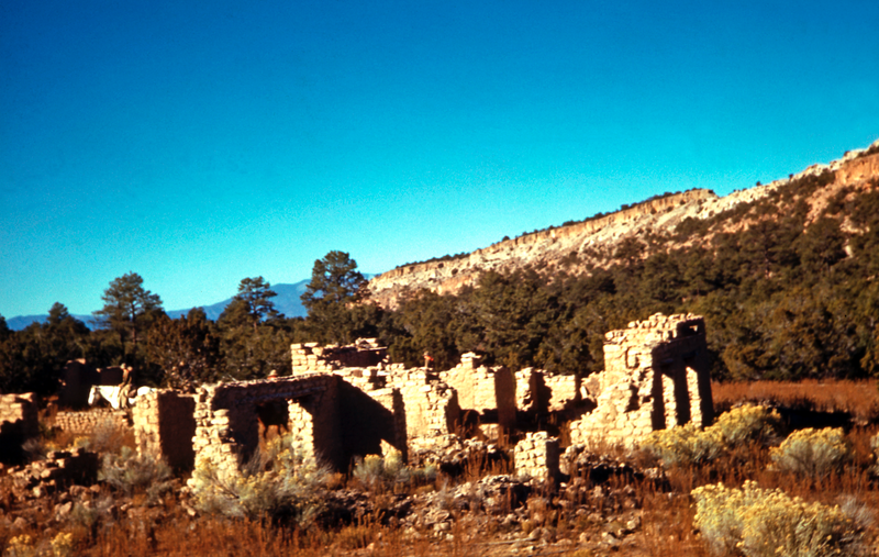Partial adobe walls are in the foreground, students on horseback ride behind the structures.