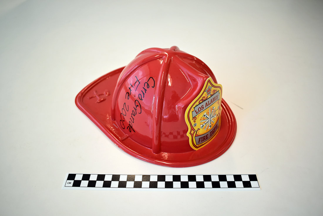 Photo of a children's Firefighter Helmet. LAHS Archives, 2000.0001.  Signed by Steve Coburn, Fire Marshall and Assistant Fire Chief, this helmet is one of many given out to children by the Los Alamos Fire Department after Cerro Grande. Los Alamos Historical Society.
